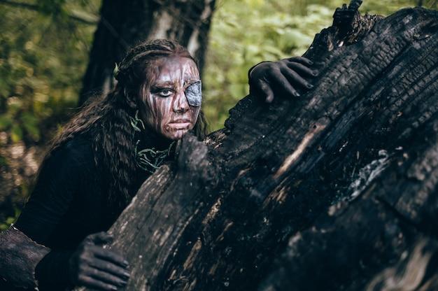 森の中でクリエイティブなメイクをしている女性のファッション写真。ファンタジー。