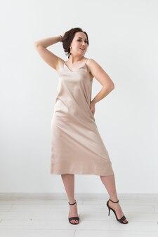 Фото моды молодой дамы в элегантном вечернем платье на белом фоне.
