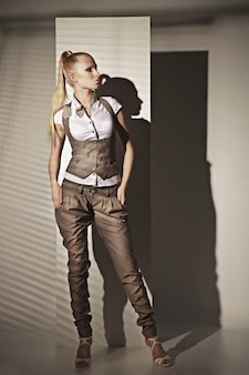 Fashion photo of sensual blonde woman in suit with shadow of jalousie