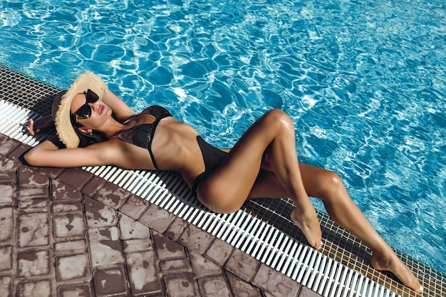 Fashion photo of sexy beautiful girl in black bikini relaxing beside a swimming pool