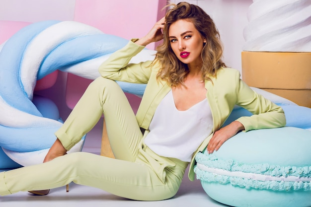 Fashion photo of sexy beautiful woman with blond curly hairstyle wearing  elegant costume  and white top sitting near big colorful  props sweets.  modern young fashionable  lady  in pastel colors .