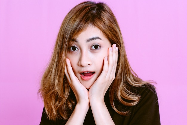 Fashion photo of surprise young girl with opened mouth on pink background