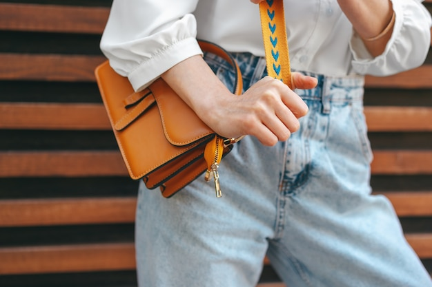 Fashion photo of woman wearing white shirt jeans and brown crossbody bag against wooden background