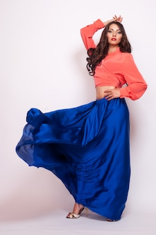 Fashion photo of young magnificent woman in blue dress.