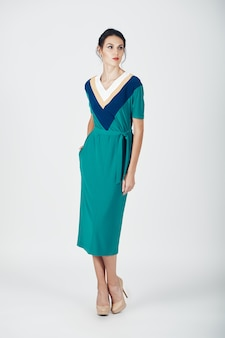 Fashion photo of young magnificent woman in a green dress
