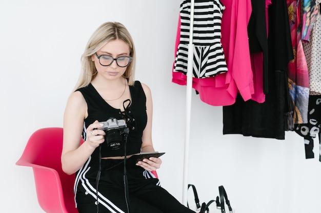 写真撮影のリファレンスを勉強しているファッションフォトグラファー。クリップボードとカメラを保持している女性。トレンディなカラフルな洋服をラックに並べたクリエイティブなワークスペース。