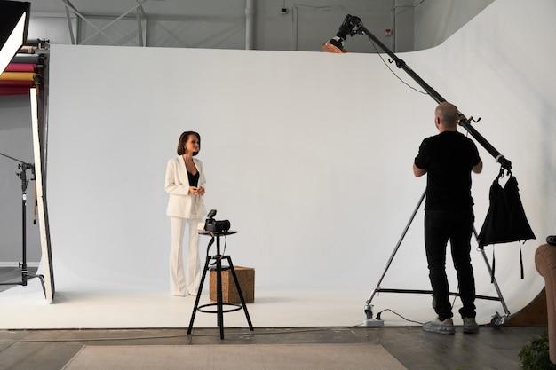 사진 스튜디오에서 패션 사진입니다. 카메라, 무대 뒤에서 아름다운 여성 모델의 사진을 찍는 전문 남성 사진 작가