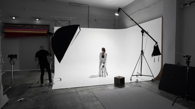 Модная фотосъемка в фотостудии. профессиональный фотограф-мужчина, снимающий модель красивой женщины на камеру, за кулисами