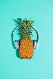 ヘッドフォンでファッションパイナップルは青い背景の上の音楽を聴きます