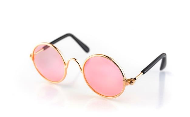 白い背景で隔離のファッションピンクの丸いメガネ