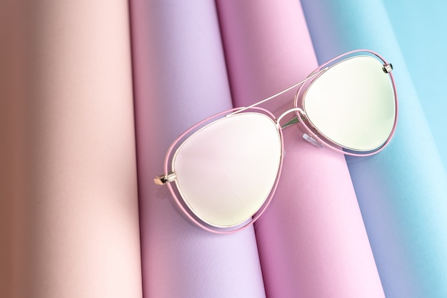 Fashion of pink sunglasses put on colorful paper background