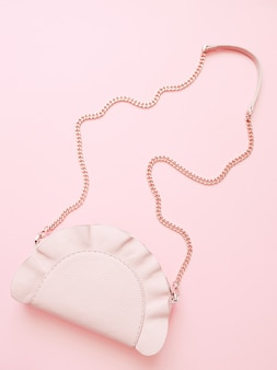 Fashion pink woman handbag on pale pink background