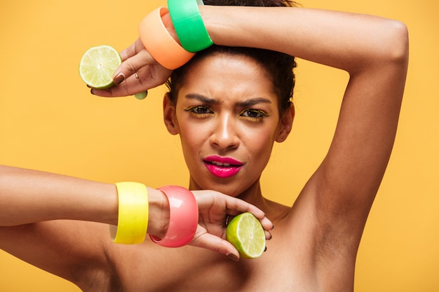 Fashion portrait of afro american woman with trendy makeup and accessories holding two halves of fresh ripe lime in both hands isolated, over yellow wall