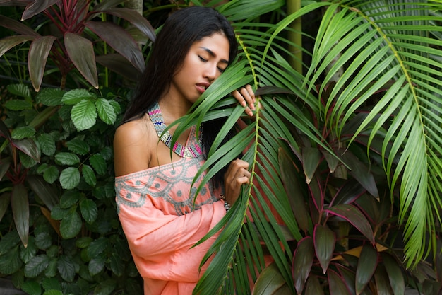 Adatti il ritratto della donna asiatica attraente che posa nel giardino tropicale. indossare abiti boho e accessori alla moda.