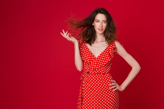Fashion portrait of attractive smiling young woman in red dotted dress on red studio