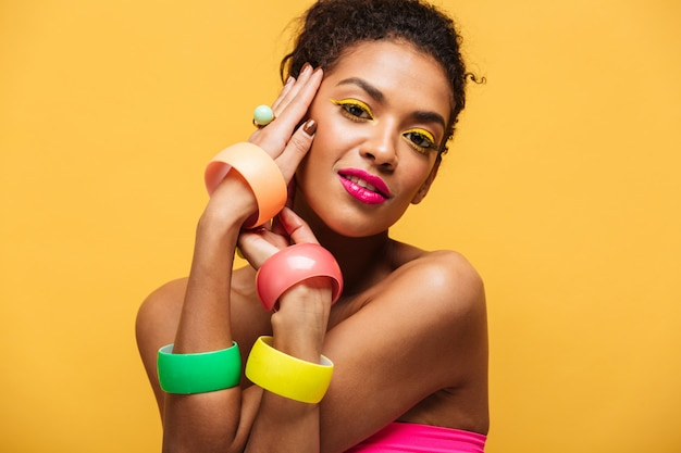 Fashion portrait of beautiful african american woman with bright makeup demonstrating multicolour jewelry holding hands at face isolated, over yellow