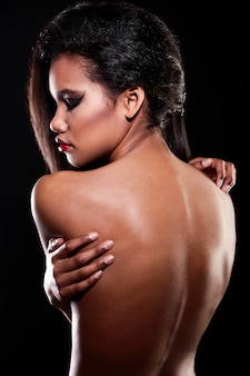 Fashion portrait of beautiful american black female brunette girl model with bright makeup red lips nude back. clean skin. black background