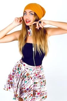 Moda ritratto di bella ragazza bionda dj hipster che tiene i suoi capelli, indossando abiti sexy luminosi e grandi auricolari bianchi.