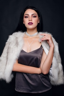 Fashion portrait of a beautiful brunette girl on fur with luxury accessories. beauty model with jewelery on black background. girl in white mink fur coat. beautiful luxury winter woman.
