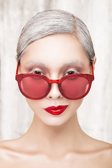 Fashion portrait of a beautiful girl with red lips and red glasses