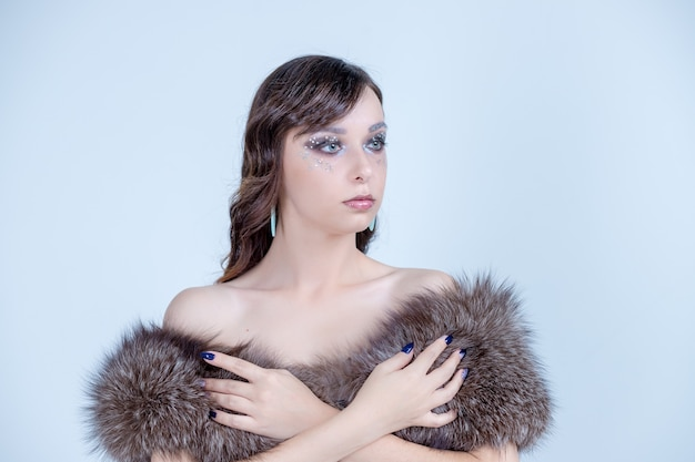 Fashion portrait of beautiful lady in fur coat. winter luxury.  woman in  fur coat. fashion model posing in eco-fur coat.holiday party make-up and manicure. winter queen.copyspace