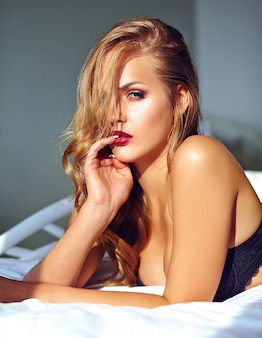 Fashion portrait of beautiful sexy young adult blond woman model wearing black erotic lingerie lying on bed at sunset