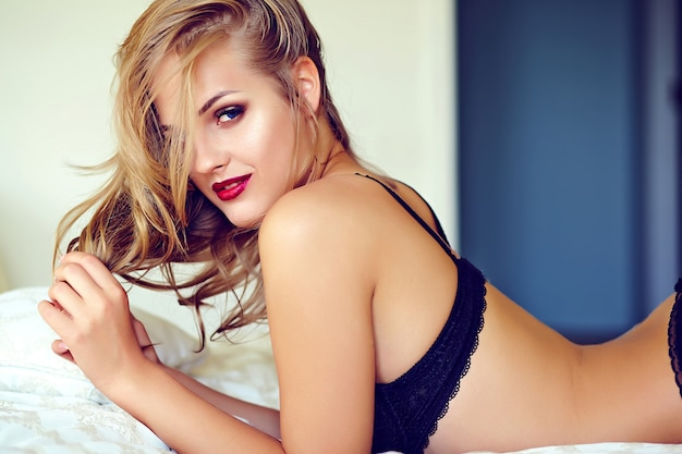 Fashion portrait of beautiful sexy young adult blond woman model wearing black erotic lingerie posing in light interior in the morning