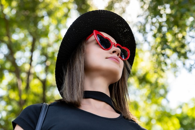 Fashion portrait of beautiful woman in black t-shirt and red skirt walking in the park. trendy clothes glasses accessories. shopping sale concept