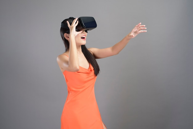A fashion portrait of beautiful woman in orange dress is wearing a virtual reality box isolated on gray.