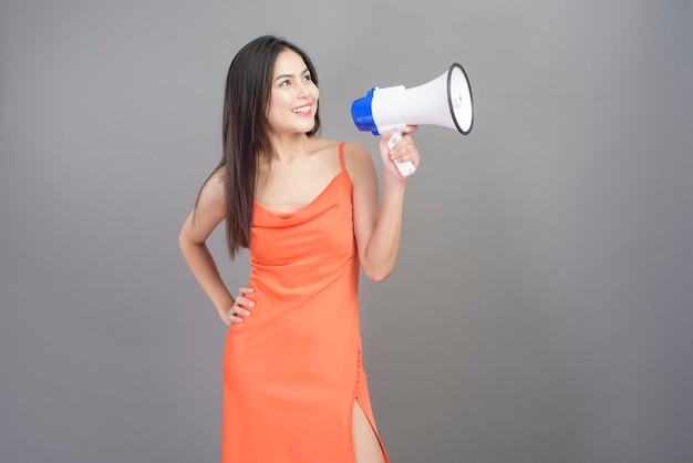 A fashion portrait of beautiful woman wearing orange dress is using megaphone isolated over gray background studio
