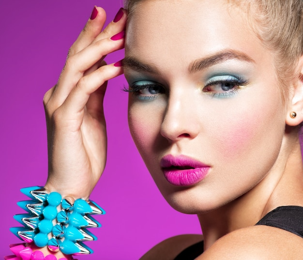 Fashion portrait of a beautiful woman with bright makeup closeup face of a beautiful fashion modelgorgeous face of an attractive girl  pink wall portrait of a girl with bracelets  thorns