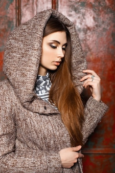 Fashion portrait of a beautiful young girl in stylish clothes with a hood