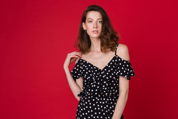 Fashion portrait of beautiful young woman in black dotted dress on red studio