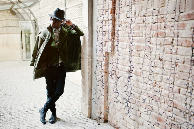 Fashion portrait of black african american man on green velvet jacket, black hat and coat cloak on his shoulders posed at arch tunnel