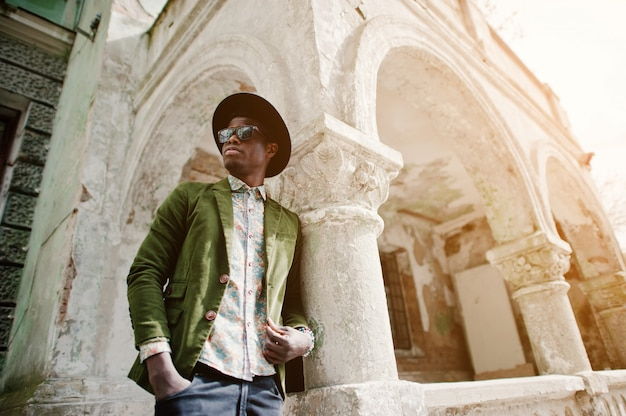 Fashion portrait of black african american man on green velvet jacket and black hat