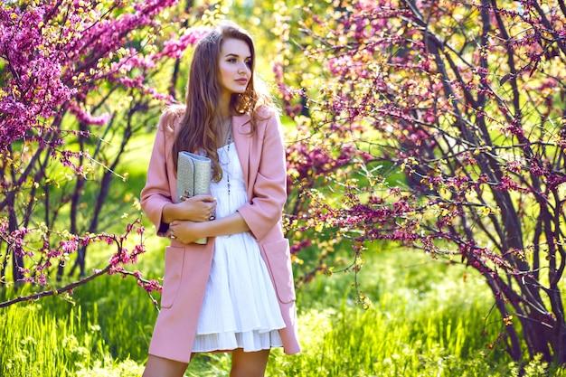 Fashion portrait of blissful stunning elegant woman posing at park with blooming sakura trees at spring time