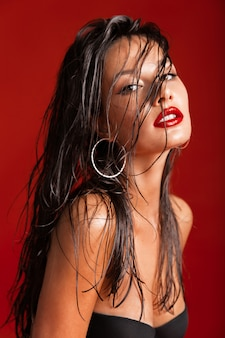 Fashion portrait of a brunette with long wet hair with big round earrings on a red background