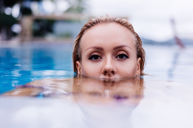 Fashion portrait of caucasian woman in bikini in blue swimming pool on vacation at coudy day natural light