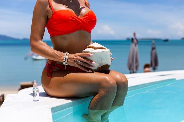 Fashion portrait of caucasian woman in bikini in blue swimming pool on vacation