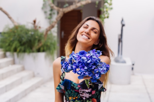 Fashion portrait of caucasian woman in stylish summer jumpsuit with flowers outside villa