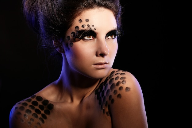 Fashion portrait of confident woman with bright black makeup and unusual hairstyle