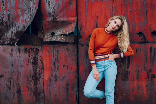 Fashion portrait of cute blonde girl posing over rusty metallic wall