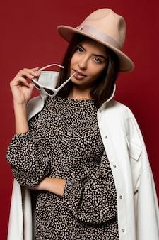 Moda ritratto di elegante donna bruna con camice bianco vestito e cappello beige che tiene occhiali da sole. stile di moda alla moda autunno o inverno.