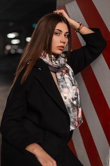道路の近くの通りのモダンな赤白の柱の近くにファッショナブルなシルクのショールでスタイリッシュな黒のコートを着たファッションの肖像画エレガントな若い女性。屋外で流行の服を着たモダンな美しい女性モデル。