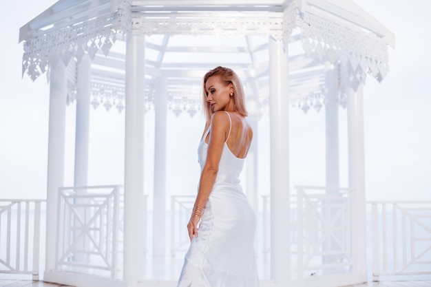 Fashion portrait of european blonde woman in silk white summer romantic dress golden bracelet and earrings