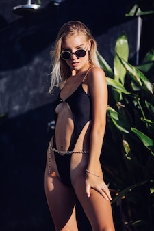Fashion portrait of fit tanned young stylish european woman in black trendy swimsuit