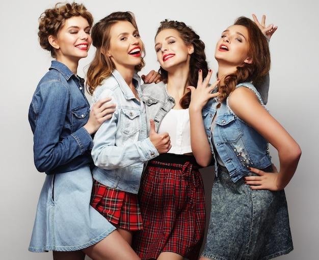 Fashion portrait of four stylish sexy girls best friends