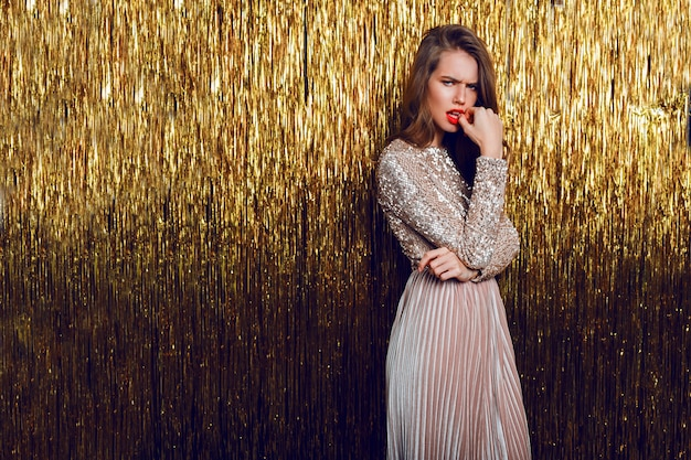 Fashion  portrait of frown woman standing  over  golden sparkling