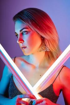 Fashion portrait girl light neon lamps blue red color.
