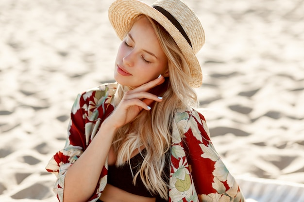 Fashion portrait of gorgeous blond woman with natural make up resting on sunny beach. wearing straw hat. holidays and vacation mood.